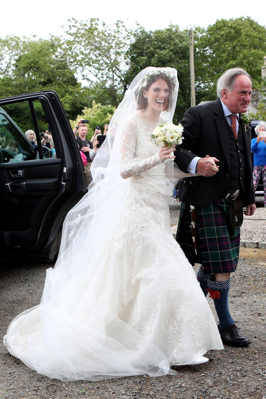 """""""Game of Thrones""""-Star Rose Leslie wird von ihrem Vater zum Altar geführt, wo Co-Star Kit Harington auf sie wartet. Sie trägt ein weißes Spitzenkleid mit langem Schleier und Blumenkranz."""