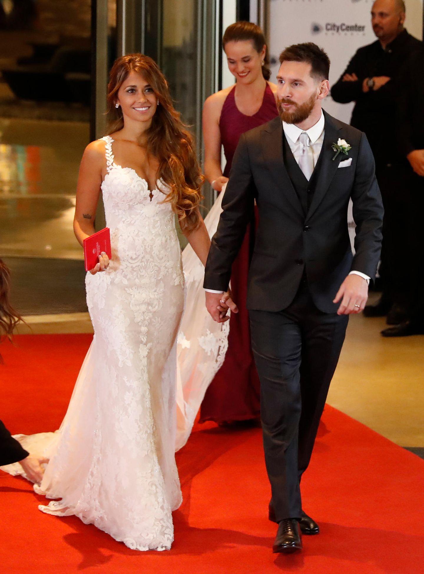Lionel Messi heiratet seine Antonella: Sie trägt ein enges weißes Kleid mit Spitzenüberzug und dünnen Trägern. Besondere Hingucker sind der spitze Ausschnitt und das roteFamilienstammbuch, das einen farblichen Akzent bildet.