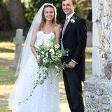 Die Hochzeit von Daisy Jenks und Charlie Van Straubenzee hatte ganz besondere Stargäste: Herzogin Meghan und Prinz Harry. Mit ihrem trägerlosen Kleid, das aufwendige Applikationen auf Top und Rock hat, schafft die Braut es trotzdem, alle Blicke auf sich zu ziehen.