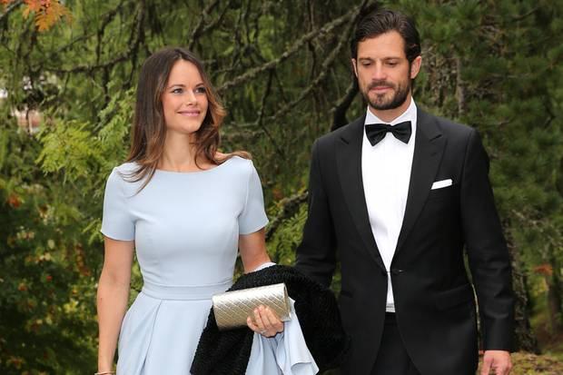 """Prinz Carl Philip und Prinzessin Sofia von Schweden sind zu Gast auf der Hochzeit von Prinz Konstantin von Bayern in St. Moritz. Sofia trägt ein zartblaues Kleid vom schwedischen Label """"By Malina"""". Der schlichte Schnitt mit T-Shirt-Ärmeln und betonter Taille schmeichelt ihrer Figur. Ihr braunes Haar trägt sie offen und dazu kombiniert sie eine glänzende Clutch."""