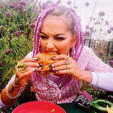 Yum Yum- Erkennen Sie den Popstar, der hier so genüsslich in den Burger beißt? Richtig, es ist Rita Ora, deren Haare perfekt mit den Blumenim Hintergrund matchen.