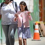 Suri ist stets top gestylt: In einem blauen Kleidchen mit Muster und einem rosa Jäckchen spaziert sie mit einer Nanny durch die Straßen New Yorks.