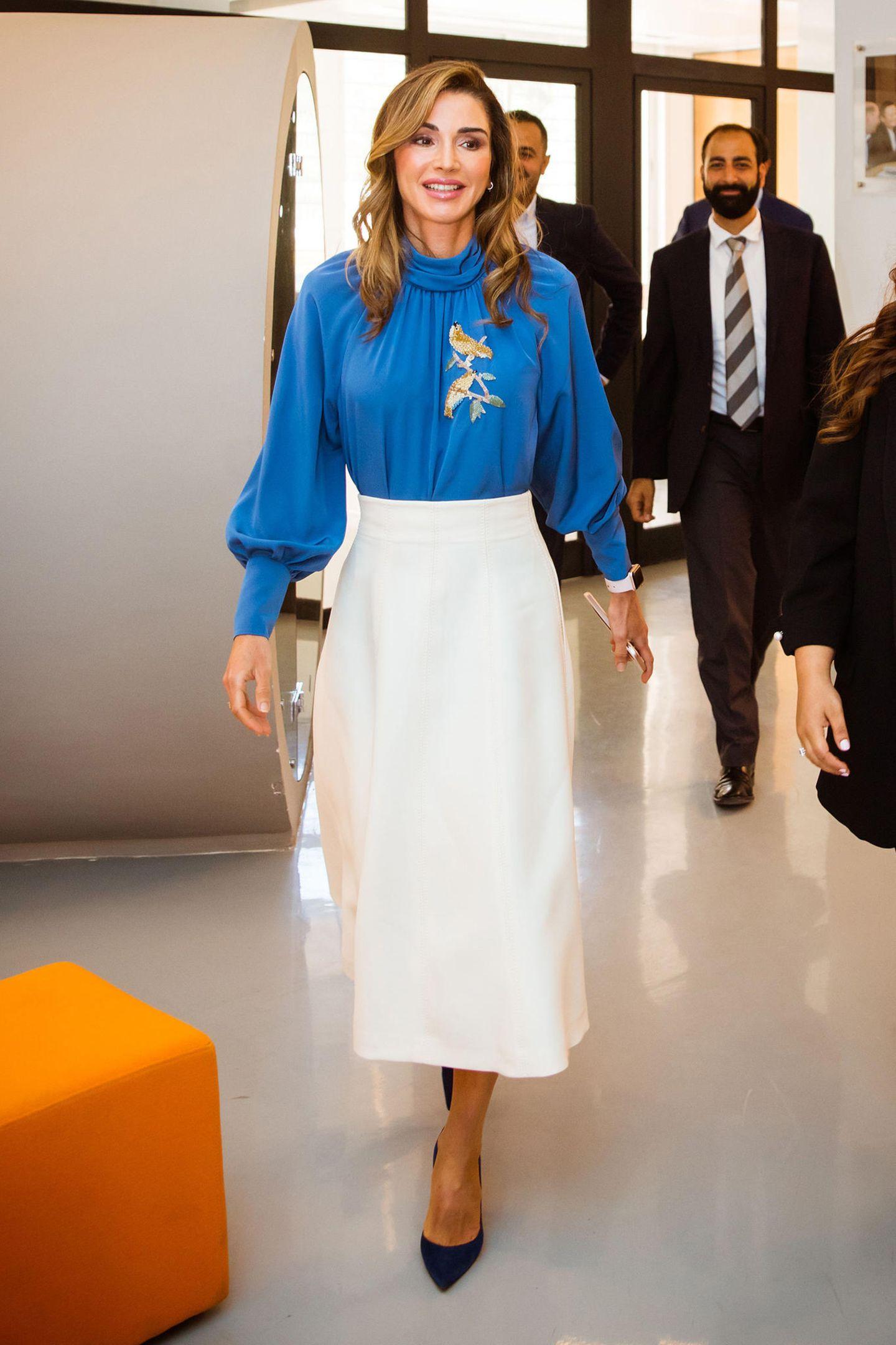 Strahlend schön in Blau-Weiß präsentiert sich Königin Rania beim Treffen mit dem Team der von ihrer Stiftung gegründetenBildungsinitiative Edraak. Die mit goldenem Vogel-Motiv verzierte Retro-Bluse stammt von der Moskauer Designerin Alena Akhmadullina.