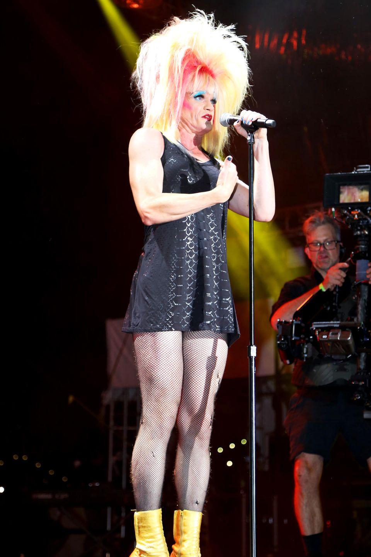 Mit einem schwarzen Minikleid, Netzstrumpfhose undgelben Stiefeln steht der Schauspieler als Dragqueen in New York auf der Bühne.