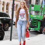 Dieser Street-Style kann sich sehen lassen! In feuerroten Stiefeletten stolziert Gigi Hadid durch die Straßen New Yorks und ist damit ein echter Hingucker. Passend zu ihren Statement-Heels hat sie eine gleichfarbige Handtasche dabei.Die roten Accessories passen einfach perfekt zusammen und werten den sonst legeren Jeans-Shirt-Look total auf.Um sich vor den ersten herbstlichen Brisen zu schützen, trägt das Model einen braunen Wollpulli über den Schultern. Übrigens: Das Wrangler-Shirt ist ein echtes Schnäppchen und für rund 35 Euro zu haben!