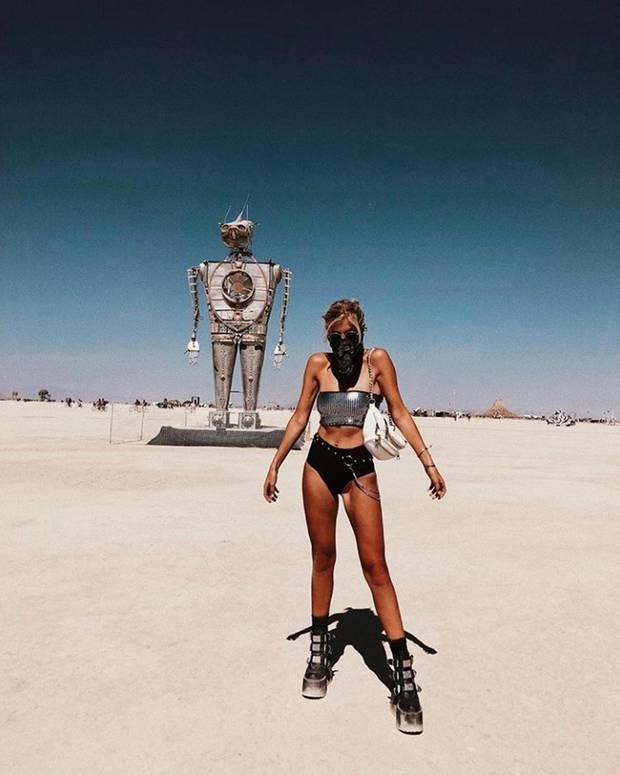 """Influencerin Xenia Overdose erfreut ihre Instagram-Fans nach einer intensiven Woche mit diesem sexy """"iRobot""""-Style vom diesjährigen Burning Man. Mit knappem Metallic-Bandeau-Top und noch knapperer Hot-Pants zu derben Plateau-Boots liegt sie voll im Trend des Kultfestivals in der Black-Rock-Wüste in Nevada."""