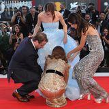 Wunderschön in einem traumhaft, blauen Kleid wird Raffey Cassidy zur Protagonistin eines kuriosen Unfalls auf dem Roten Teppich bei den Filmfestspielen in Venedig. Plötzlich bleibt die Schauspielerin mit ihrem Kleid stecken und kann sich nicht weiter bewegen. Jedoch naht schnelle Hilfe von ihren Co-StarsBrady Corbet, Natalie Portman und Stacy Martin. Die Drei befreien Raffey aus dieser misslichen Situation. Noch mal Glück gehabt.