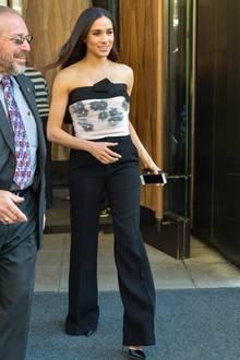 Ein ganz ähnliches Outfit hat Meghan bereits drei Jahre zuvor an. In 2015 ist es jedoch kein Trio, sondern ein Duo. Die Hose und das Bandeau-Oberteil bleiben gleich, nur das Sakko lässt sie damals noch weg. Zu diesem muss sie in royalen Zeiten jedoch greifen. Schließlich muss das Outfit schick und seriös sein. Freie Schultern wären da weniger angebracht!
