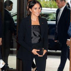 Bei einem Charity-Event in London erscheint Herzogin Meghan in einem Style-Trio - bestehend aus Blazer, Anzughose und trägerlosem Seidenoberteil. Unterwegs ist sie auf spitzen Pumps.