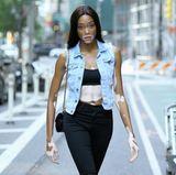 Model Winnie Harlow auf dem Weg zum Callback. Sie kombiniert eine schwarze Jeans zum knappen Bandeau-Top und lässiger Jeans-Weste. Schnürstiefel in schwindelerregender Höhe runden ihren Casting-Look ab.