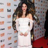"""Im zarten Kleid von Jonathan Simkhai setzt Olivia Munn auf einen schönenKontrast zum """"Predator"""" im Hintergrund."""