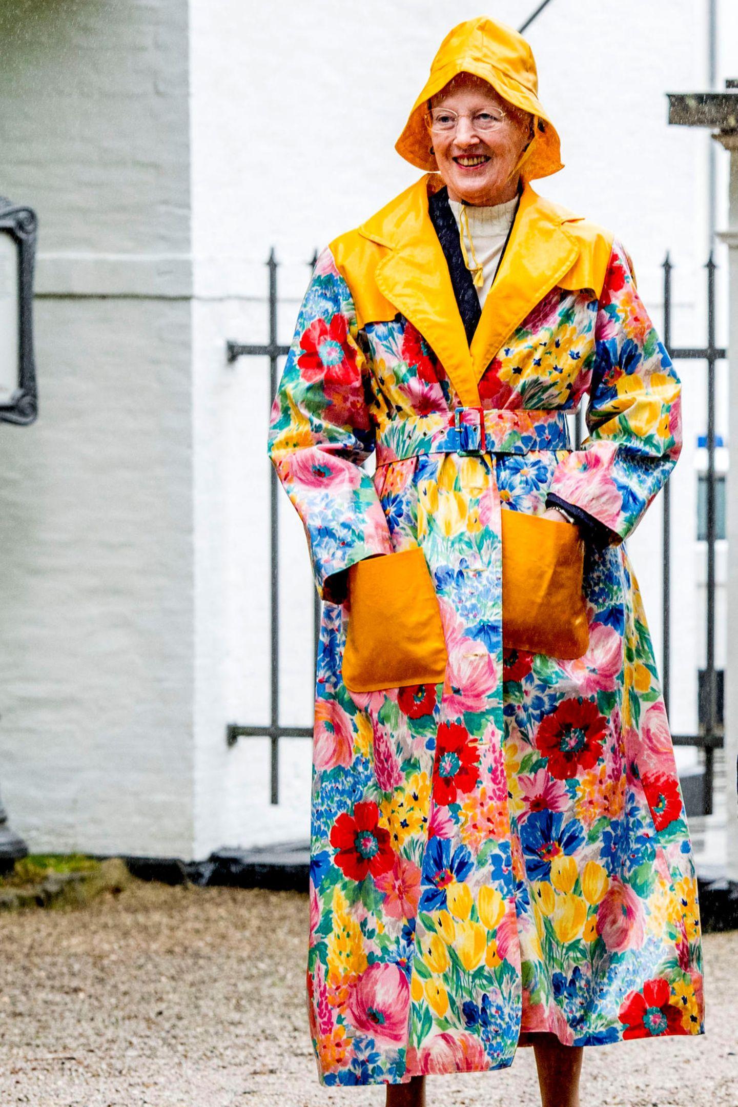 Keiner trotzt dem Regen so schön wieKönigin Margrethe. Mit einem gelben Regenhut und passendem Blumen-Regenmantel empfängt sie Graastens Ringreiterverein vor Schloss Graasten.