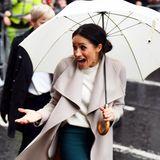 Das schlechte Wetter bei einer Wanderung in Belfast kann der guten Laune von Herzogin Meghan nichts anhaben, schließlich ist sie mit einem großen Regenschirm bestens gerüstet.