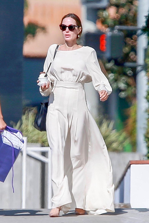 In einem weißen, wallenden Kleid schlendert Angelina Jolie durch die Straßen von Los Angeles. Das bodenlange Dress mit weiten Ärmeln betont ihre sehrschmale Silhouette besonders an der Taille. Hoffentlich landet das Eis aus ihrem Becher direkt auf den Hüften!