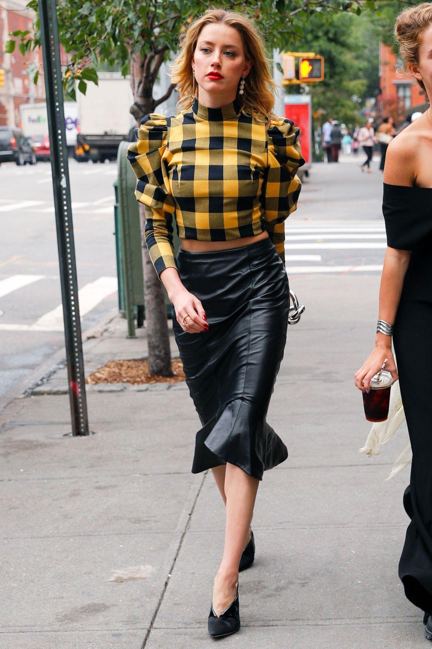 Amber Heard zeigt sich stylischer denn je auf den Straßen von New York City. In einemsexy Leder-Pencil-Skirt und karierter Crop-Bluse mit Puffärmeln stolziert sie selbstbewusst durch die Stadt die niemals schläft. Rote Lippen und High-Heels mit V-Ausschnitt runden ihren Streetstyle ab.