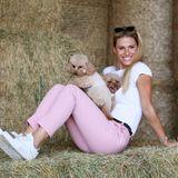 Herrlich normal! In einem stylischen Freizeitlook und mit wenig Make-up spielt Michelle Hunziker mit ihren Hunden im Heu. Sie trägt eine rosafarbene Hose, ein weißes T-Shirt und weiße Sneaker.