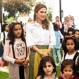 Beim Besuch eines Waisenhauses in Jordanien glänzt Königin Rania nicht nur mit ihrer liebevollen Art, sondern auch mit ihrem Look. Zu einer weißen, schlichten Buse kombiniert sie einen echten Hingucker-Rock.
