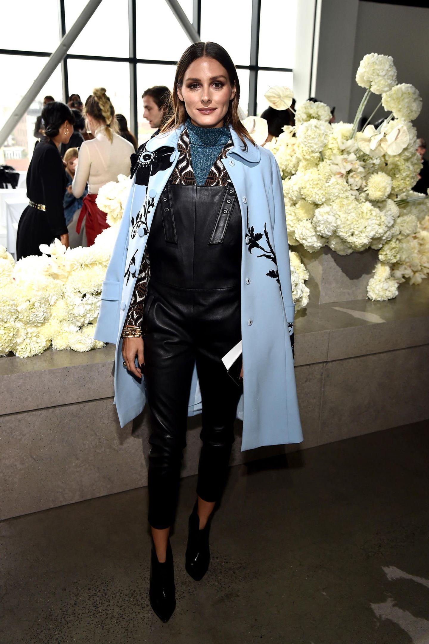 Stilikone Olivia Palermo kombiniert zur Leder-Latzhose einen hellblauen Mantel und einen Strickpulli. Auch sie zählt zu den Gästen der Show von Zimmermann.