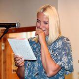 Hi hi hi Prinzessin Mette-Marit liest bei einer Veranstaltung in einer Schule ihre eigenen Aufsätze aus vergangenen Schultagen. Diese scheinen so lustig zu sein, dass sich Mette kaum halten kann, vor Lachen.