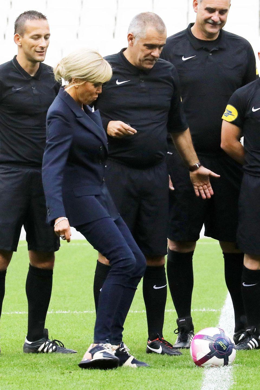 Mit diesem Style istBrigitte Macron am Ball! Im dunkelblauen Anzug eröffnet die Première Dame zugunsten der Pierre-Deniker-Stiftung ein Benefizspiel im Stade de France in Saint Denis.