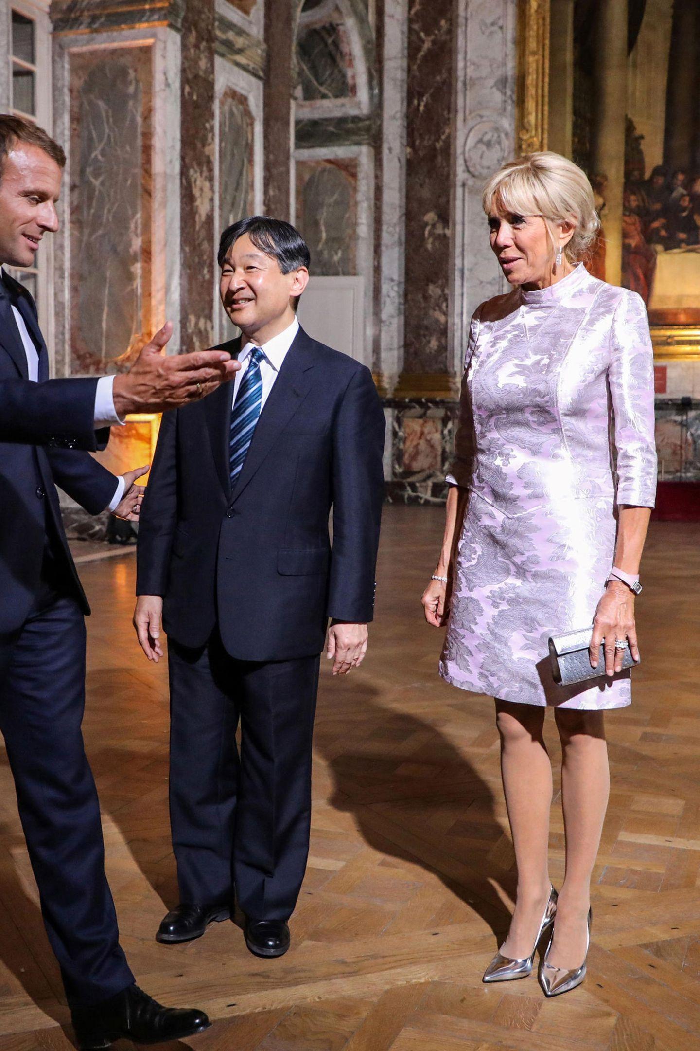 Nach dem Fußball-Spaß im Stade de France hatdie Première Dame für das Gala-Dinner mit Kronprinz Naruhito im SchlossVersailles am Abend ihren Sportlook gegen diesen asiatisch angehauchten Seiden-Look in kühlem Rosé eingetauscht.