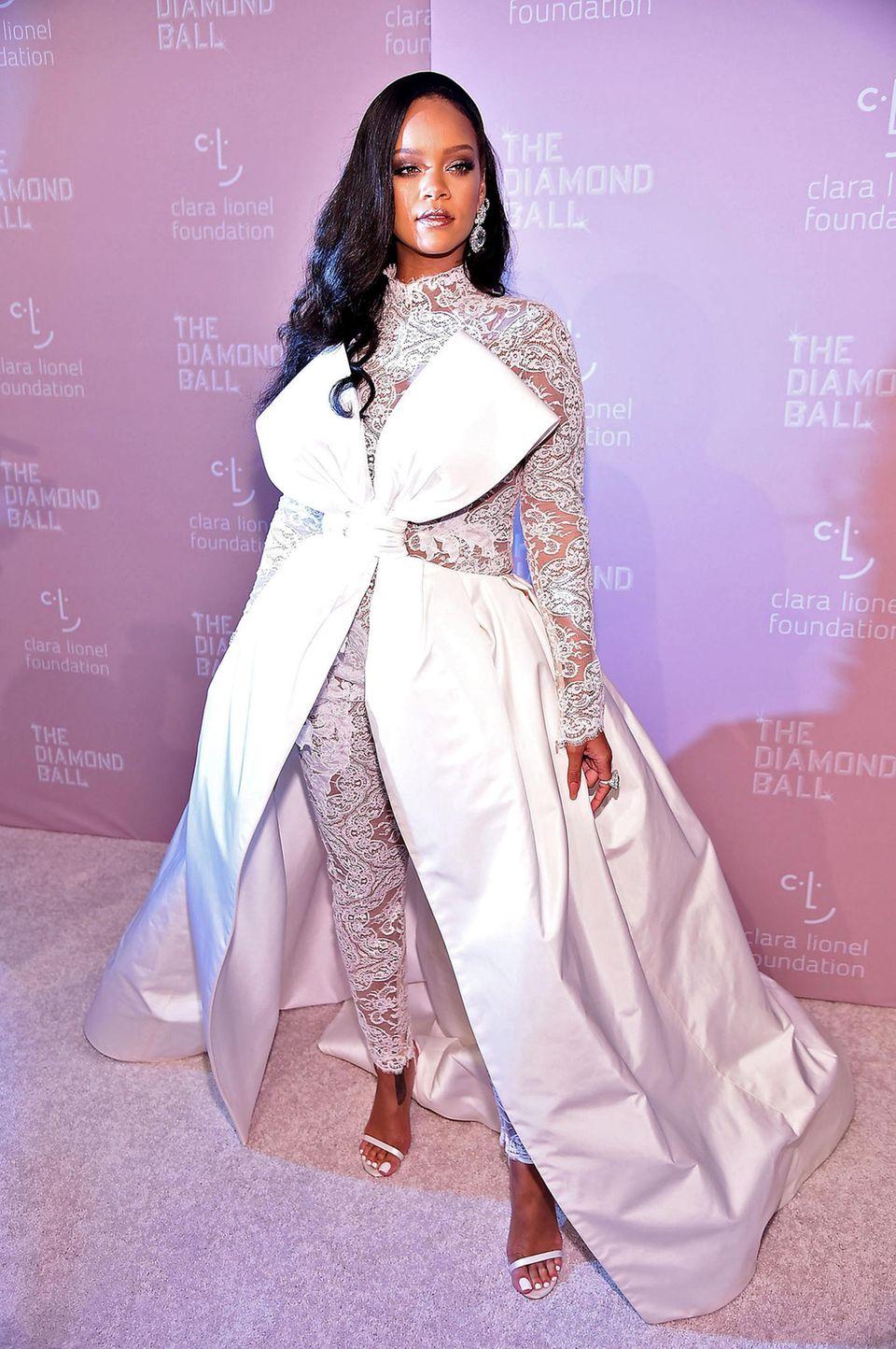 Für die Gäste ihres 4. Diamond Balls hat sich Rihanna mit weißem Spitzen-Jumpsuit und überdimensionaler Schleife von Alexis Mabille Couture ganz besonders eindrucksvoll verpackt. Da gehen die funkelnden Diamant-Ohrringe von Chopard fast schon unter.