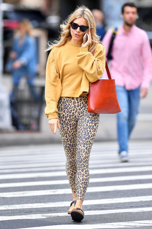 Sienna Miller zeigt, wie man den Leo-Trend ganz simpel im Alltag tragen und kombinieren kann. Zu einer Hose mit Leo-Print kombiniert sie einen farblich harmonierenden Pullover und setzt mit einer roten Handtasche Akzente.