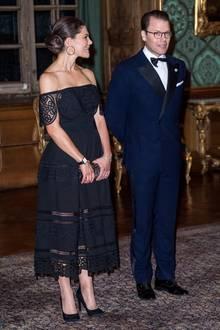 Prinzessin Victoria legt in einem schwarzen Off-Shoulder-Kleid mit Spitzenapplikationen einen sehr heißen Auftritt hin. Das schwarze Kleid bezirzt durch durchsichtige Linien im ausgestellten Rock und Spitzenränder.