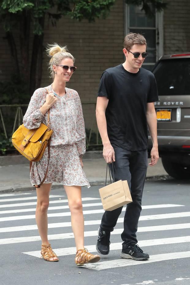 Nicky Hilton und ihr Ehemann James Rothschild schlendern gut gelaunt durch New York. Sie zeigt sich sommerlich in Kleidchen und mit gelben Akzenten, er ist ganz in Schwarz gekleidet.