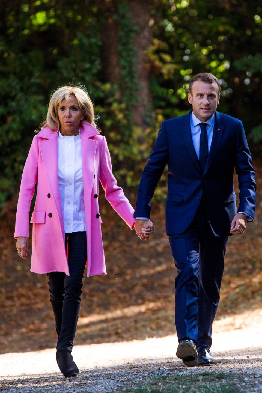 """Während der """"French Heritage Days"""" in Bougival erstrahlt Brigitte Macron in einem knallpinken Mantel. Dazu kombiniert sie ein schlichtes Ensemble aus Bluse und dunkler Hose."""