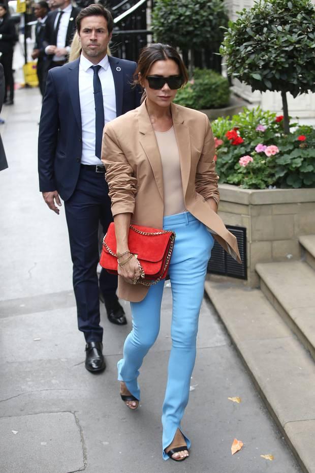 Zu der Präsentation ihrer Catwalk-Kollektion greift Victoria Beckham zu einem Look, der ziemlich ungewöhnlich für sie ist. Ihre Hose ist nicht einfach nur farbig, sondern richtig knallig. Für die komplette Farbexplosion sorgt ihre Handtasche.