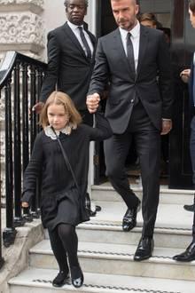Zu der Fashion Show ihrer Mutter geht Harper Beckham in einem schicken Kleidchen mit hübschen Bubikragen aus Häkelspitze. Dazu passen die Lackschühchen besonders gut. Alles ist in einem mädchenhaft eleganten Stil gehalten.