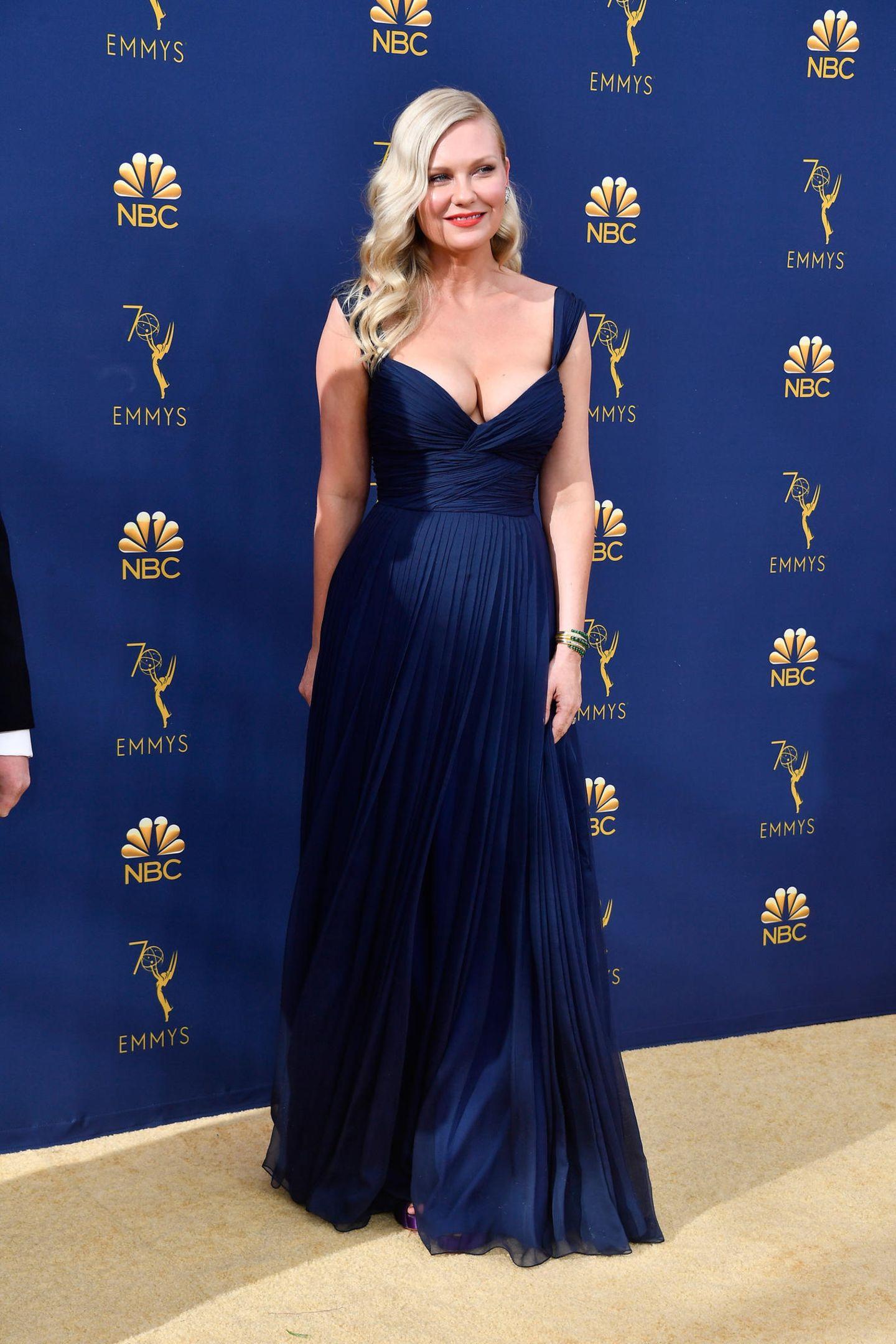 Bei ihrem Auftritt auf den 70. EmmyAwards sehen wir nichts von überflüssigen After-Baby-Pfunden.Nur vier Monate nach der Geburt von SohnEnnis Howard Plemons strahltKirsten in diesem royal-blauen, bodenlangen Kleid mit fließendem Schnitt. Das Kleid stammt aus der Feder des Pariser Modelabels Schiaparelli.