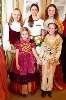 """Eine echte Prinzessin, und viele, die es gerne wären! Für eine Tanzaufführung wählt Sofia von Schweden das blau-weiße """"Susanna""""-Kleid des britischen Labels LK Bennett für rund 250 Euro. Dazu trägt sie einen Pferdeschwanz und geht zwischen den pompösen Roben der Darsteller fast unter. Den kleinen Damen sei der große Auftritt gegönnt!"""