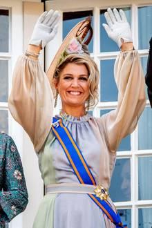 Das edle Kleid aus fließendem Stoff überzeugt in sanften Pastelltönen. Máximas Robe stammt von Designerin Luisa Beccaria. Die Königin kombiniert funkelnde Ohrringe und einen großen Fascinator zu ihrem Look - ihr wohl schönsten Accessoire ist jedoch ihr strahlendes Lächeln.
