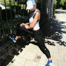 Model Lena Gercke wärmt sich vor dem Joggen mit einem Stretching auf.