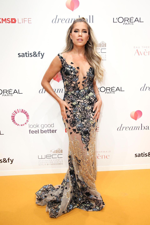 Dreamball 2018: Sylvie Meis ist nun seit 2009 Schirmherrin des Dreamballs. Wie in jedem Jahr feiert sie diese Ehre in einem ganz besonderen Look. In 2018 ist es ein Kleid von Designerin Jasmin Erbaş Couture, das sich wie filigrane Blumenranken um ihren Körper legt.