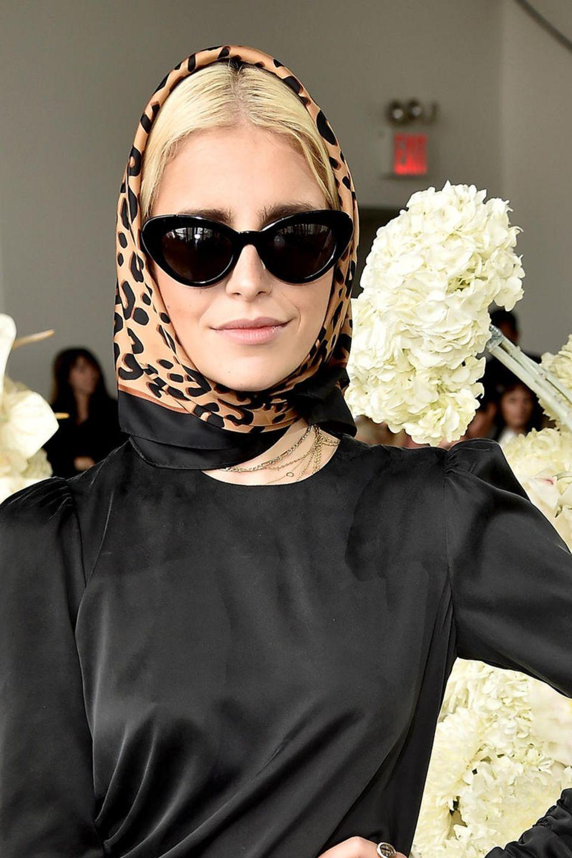 Caro Daur peppt ihren eleganten, schwarzen Look mit einem Leo-Kopftuch auf.