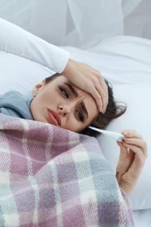 Frau mit Fieber im Bett (Symbolbild)