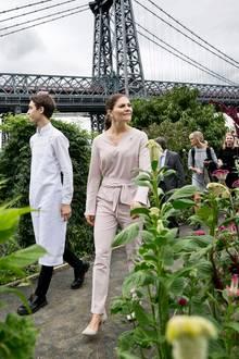 Prinzessin Victoria ist nach New York gereist und in Brooklyn unterwegs. Im Garten nahe der Manhattan Bridge gibt sie - trotz September-Wolken - einen frühlingshaften Anblick ab. das liegt auch an ihrem hellen Zweiteiler in Blush. Locker leicht wickelt sie das Oberteil in der Taille, die Hose schwingt beim Gehen luftig mit.