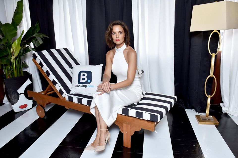 Black and White: Zur Alice + Olivia Präsentation im Rahmen der New York Fashion Week trägt Katie Holmes ein weißes Midi-Kleid mit beigefarbenen Pumps. Rote Lippen runden ihren Look ab.