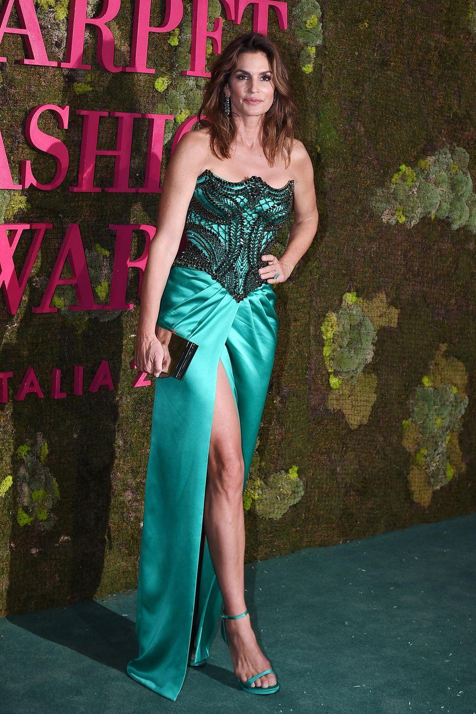 Cindy Crawford präsentiert sich für die #GreenCarpetChallenge im türkisfarbenen Satin- und Seide-Look von Versace, natürlich aus zertifizierten Naturfasern und aufwendig bestickt mit bleifreien Kristallen von Swarovski.