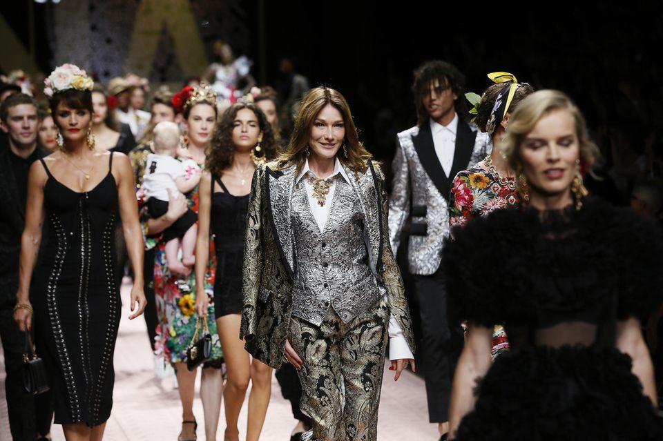 Während der Show von Dolce & Gabbana geht es wirklich buntzu: Aktuelle Topmodels, Royals und Supermodels der 90er-Ära erobern zusammen den Laufsteg. Carla Bruni scheint das in ihrem silbernen Anzug gefallen.