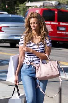 Die vorderen Haarsträhnen hat Tyra lässig zusammengebunden, damit sie ihr während der Einkaufstour nicht in die Augen fallen. Ein bequemes Streifenshirt, eine Jeans und Sneaker machen den Shopping-Look perfekt!