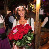 Sarah Lombardi posiert mit einem Rosenstrauß im Käferzelt.