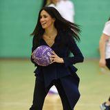 """Bei den """"Coach Core Awards"""" der Loughborough Universität, bei dem unter anderemAbsolventen eine Partie Netball spielen, kleidet sich Herzogin Meghanin einer Oscar de la Renta Bluse mit asymmetrischen Schößchen und Taillengürtel. Dazu kombiniert sie eineSchlaghose und - Pumps. Ob sie vorher wusste, dass es sich bei dem Termin um eine Sport-Veranstaltung handelt?"""