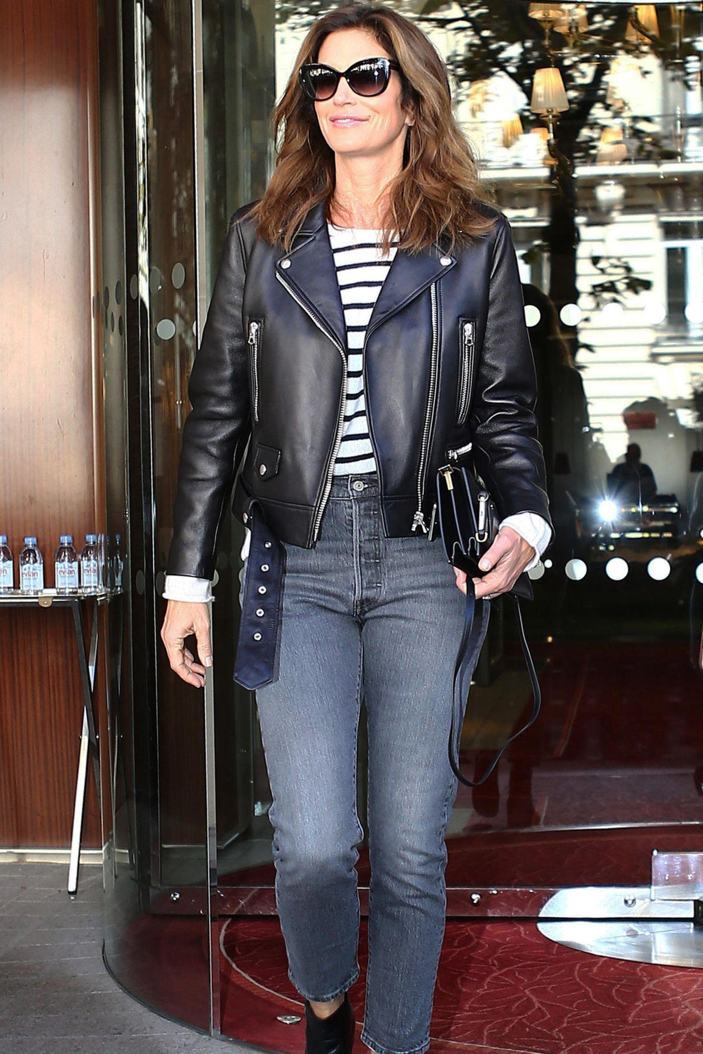Cindy Crawford rockt Paris in diesem lässigen Look. Zur Jeans kombiniert sie ein gestreiftes Shirt, Lederjacke und Sonnenbrille. Ihre Handtasche trägt sie locker als Clutch.