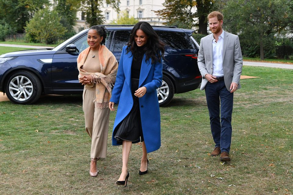 Zusammen mit ihrer Mutter Doria und ihrem Mann, Prinz Harry, schreitet Herzogin Meghan zu ihrer kleinen Charity-Kochstunde.
