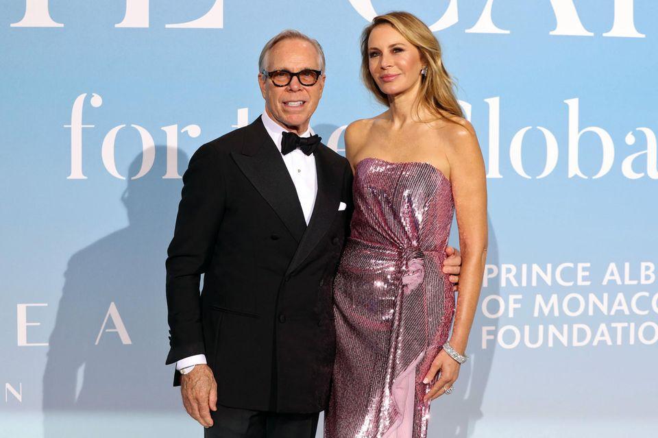 Designer Tommy Hilfiger hält seine glamourös in Pink gestylte Frau Dee im Arm.