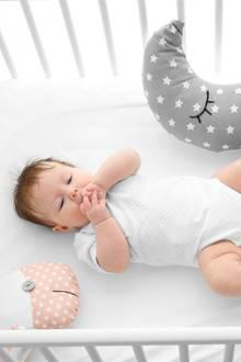Baby liegt auf dem Rücken im Bett